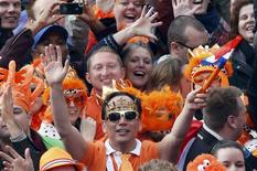 A man wears a crown as he celebrates the new Dutch King Willem-Alexander who succeeds his mother Queen Beatrix, in Amsterdam's Dam Square April 30, 2013. REUTERS/Kevin Coombs