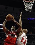Jason Collins (E), do Washington Wizards, sobe para cesta com Taj Gibson, do Chicago Bulls, durante partida da NBA em Chicago. 17/04/2013 REUTERS/Jim Young