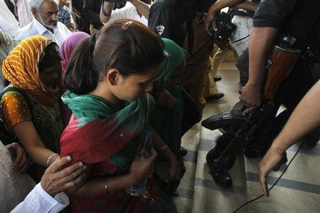 Pakistani security officials escort Poonam (C), a daughter of Sarabjit Singh, who was convicted of spying for India and sentenced to death in Pakistan, as she arrives with her family members at Jinnah hospital in Lahore April 28, 2013. REUTERS/Mohsin Raza
