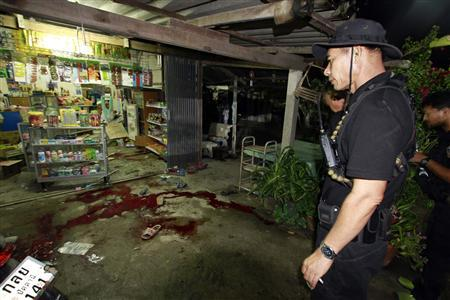 Thai security personnel inspect a grocer's shop where six people were shot dead by suspected Muslim militants in the southern province of Pattani May 1, 2013. REUTERS/Surapan Boonthanom