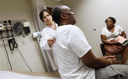 A man recieves a check up as his wife looks on at University of Chicago Medicine Primary Care Clinic in Chicago June 28, 2012. REUTERS/Jim Young