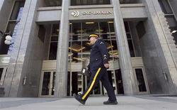A Royal Canadian Mounted Police (RCMP) officer walks past the headquarters of SNC Lavalin in Montreal April 13, 2012. REUTERS/Christinne Muschi