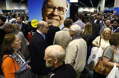 "A huge picture of Berkshire Hathaway Chairman Warren Buffett looks over shareholders swarming the exhibit floor where companies owned by Berkshire display and sell their products, at the company's annual meeting in Omaha May 4, 2013. Buffett and the board of his conglomerate Berkshire Hathaway Inc are ""solidly in agreement"" on who should be the company's next chief executive, he said at Berkshire's annual shareholder meeting on Saturday. REUTERS/Rick Wilking"