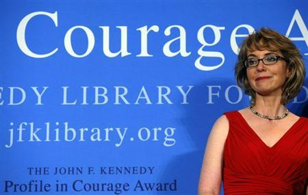 2013 John F. Kennedy Profile in Courage Award recipient, former U.S. congresswoman Gabrielle Giffords, listens as her husband Mark Kelly speaks at the awards ceremony at the Kennedy Library in Boston, Massachusetts May 5, 2013. REUTERS/Brian Snyder