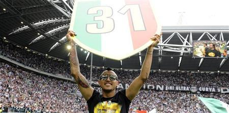Juventus' Arturo Vidal holds the ''Scudetto'' emblem at the end of the team's Italian Serie A soccer match against Palermo at the Juventus stadium in Turin May 5, 2013. REUTERS/Giorgio Perottino