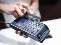 Кассир проводит банковскую карту через платежный терминал в магазине в Сиднее, 11 декабря 2012 года. Российская платежная система QIWI разместила ADS по $17, таким образом её акционеры получили от IPO на Nasdaq $212,5 миллиона. REUTERS/Tim Wimborne