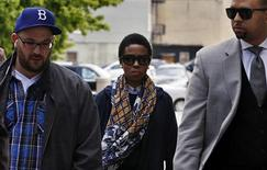 Hip hop artist Lauryn Hill, escorted by her private security, arrives at United States Court in Newark, New Jersey, May 6, 2013, for a scheduled sentencing on federal tax evasion charges. The Grammy-winning musician is scheduled for sentencing on Monday in U.S. District Court in Newark, New Jersey on three charges she failed to file tax returns on more than $1.8 million between 2005 and 2007. REUTERS/Mike Segar