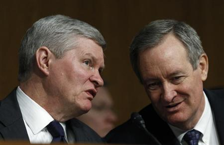 Senate Banking, Housing and Urban Affairs Committee Chairman Tim Johnson (L) (D-SD) talks with Senator Mike Crapo (R-ID) during Federal Reserve Board Chairman Ben Bernanke appearance before a committee hearing on ''The Semiannual Monetary Policy Report to the Congress.'' in Washington February 26, 2013. REUTERS/Gary Cameron