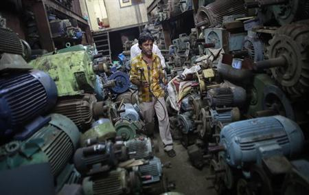 An employee works inside a motor pump workshop at an industrial area in Mumbai May 3, 2013. REUTERS/Danish Siddiqui/Files