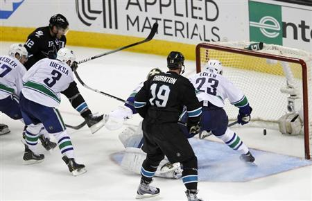 San Jose Sharks' Patrick Marleau (L, in black) scores the winning goal in overtime over the Vancouver Canucks during Game 4 of their NHL Western Conference quarterfinal hockey playoff game in San Jose, California May 7, 2013 REUTERS/Robert Galbraith