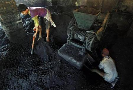 Labourers work inside a coal ball factory in Kolkata November 4, 2010. REUTERS/Rupak De Chowdhuri/Files