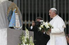 Pope Francis offers flowers to a statue of Our Lady of Lujan during his Wednesday general audience in St Peter's Square at the Vatican May 8, 2013. REUTERS/Stefano Rellandini