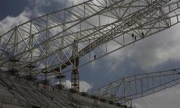 Operários trabalham na construção do novo estádio do Corinthians, em preparação para receber jogos da Copa do Mundo de 2014, no bairro de Itaquera, em São Paulo. A Fifa manifestou preocupação com relatos de que o estádio de São Paulo não será concluído dentro do prazo até dezembro, em mais uma cobrança da entidade para que o Brasil acelere o ritmo dos preparativos para o torneio. 27/03/2013. 27/03/2013. REUTERS/Nacho Doce