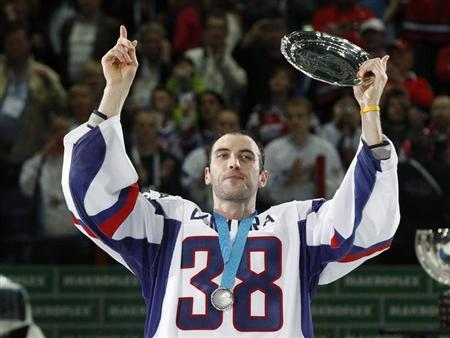 Slovakia's Zdeno Chara wears jersey with the number of the former Slovak national team captain Pavol Demitra as he holds a trophy after their lost 2012 IIHF men's ice hockey World Championship final game with Russia in Helsinki May 20, 2012. REUTERS/Petr Josek