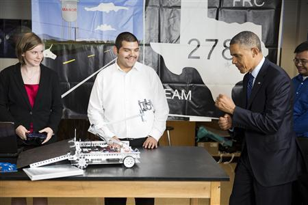 U.S. President Barack Obama puts up his fists during a demonstration of a robot by students at Manor New Tech High School in Austin, Texas, May 9, 2013. REUTERS/Joshua Roberts