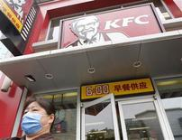 A woman wearing a mask walks out of a KFC restaurant in Beijing, May 9, 2013. REUTERS/Kim Kyung-Hoon