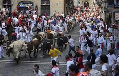 Runners sprint alongside Torrehandilla fighting bulls on Mercaderes street during the final running of the bulls at the San Fermin festival in Pamplona July 14, 2012. REUTERS/Vincent West