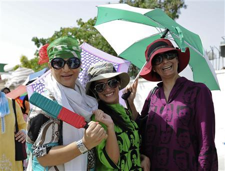Supporters of Imran Khan, a Pakistani cricketer-turned-politician and chairman of the Tehrik-i-Insaf (PTI) political party, react as they pose for a camera outside a polling station during general election in Karachi May 11, 2013. REUTERS/Insiya Syed