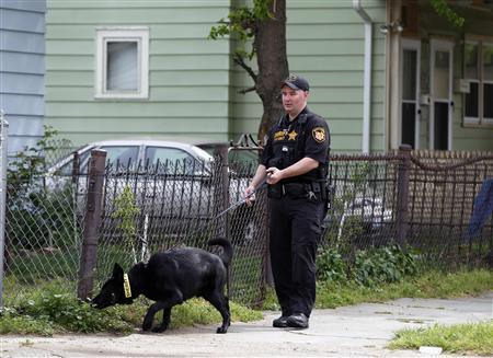 A Cuyahoga County Sheriff's deputy leads a dog through the neighborhood outside Ariel Castro's home in Cleveland, Ohio, May 10, 2013. REUTERS/Matt Sullivan