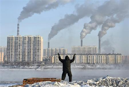 An elderly exercises in the morning as he faces chimneys emitting smoke behind buildings across the Songhua river in Jilin, Jilin province, February 24, 2013. REUTERS/Stringer