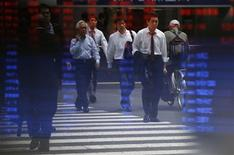 Passers-by are reflected on a stock quotation board at a brokerage in Tokyo May 13, 2013. REUTERS/Issei Kato