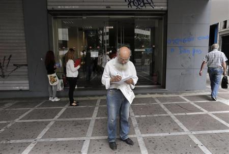 A man checks a document as he leaves a Greek Manpower Employment Organisation (OAED) office in central Athens May 9, 2013. REUTERS/John Kolesidis