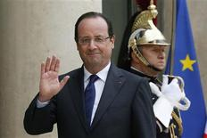 French President Francois Hollande (R) waves goodbye at journalists in the courtyard of the Elysee Palace in Paris May 10, 2013. REUTERS/Gonzalo Fuentes