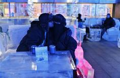 Honeymooner Ahmed, form Saudi Arabia who got married last week, kisses his veiled bride at Chillout cafe in Dubai May 12, 2013. Chillout, owned by UAE's Sharaf Group, is the first ice lounge in the Middle East, with temperatures set at -6 degrees Celsius (21 degrees Farenheit). The cafe, with its illuminated interiors, curtains, paintings and seating arrangements, is all made of carved ice and frozen sculptures. REUTERS/Ahmed Jadallah