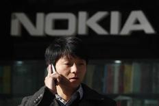 Человек говорит по мобильному телефону на фоне логотипа Nokia в Шанхае 6 декабря 2012 года. Доля Nokia на рынке мобильных телефонов сократилась почти на 5 процентных пунктов в первом квартале, сообщила во вторник исследовательская компания Gartner. REUTERS/Aly Song