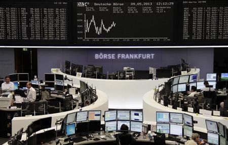 Traders are pictured at their desks in front of the DAX board at the Frankfurt stock exchange May 9, 2013. REUTERS/Remote/Pawel Kopczynski