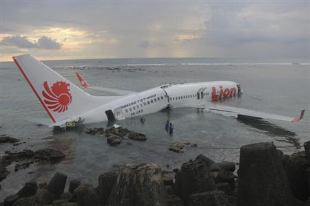 A Lion Air plane is seen in the water after it missed the runway in Denpasar, Bali in this picture provided by the Indonesian police April 13, 2013. REUTERS/Indonesian Police/Handout