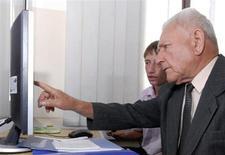 """Студент знакомит пожилого человека с навыками владения компьютером в рамках акции """"Поколение ON-LINE"""" в классе гимназии №1 во Владивостоке 28 сентября 2010 года. Полиция возбудила уголовное дело против интернет-пользователя, обвинив в публикации призывов к расправе над полицейскими в порядке мести за преследование """"приморских партизан"""", представших перед судом присяжных. REUTERS/Yuri Maltsev"""