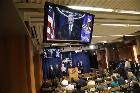 U.S. Attorney General Eric Holder appears on television monitors as he stands at the lectern to address a news conference to announce Medicare Fraud Strike Force law enforcement actions at the Justice Department in Washington May 14, 2013. REUTERS/Jonathan Ernst