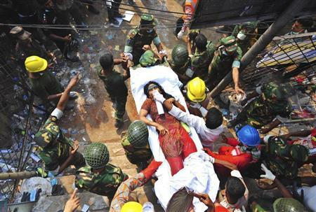 Rescue workers carry a garment worker, who was pulled alive from the rubble of the collapsed Rana Plaza building, in Savar, 30 km (19 miles) outside Dhaka April 27, 2013. REUTERS/Stringer