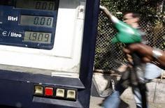 Водитель готовится заправить автомобиль на заправке в Риме, 13 марта 2013 года. Фьючерсы на нефть эталонной марки Brent опустились до $103 за баррель в четверг, поскольку более резкий, чем ожидалось, спад промпроизводства США ухудшил прогноз спроса, однако неожиданное сокращение запасов сырья в крупнейшем мировом потребителе помогло замедлить снижение. REUTERS/Tony Gentile