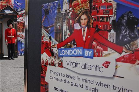 A man dressed as a guard stands next to a Virgin Atlantic promotional poster in Union Square to celebrate the Diamond Jubilee of Queen Elizabeth in New York June 2, 2012. REUTERS/Eduardo Munoz