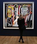 """Visitante olha quadro """"Dustheads"""" de Jean-Michel Basquiat (1982) durante exibição prévia de Arte Contemporânea e Pós-Guerra da casa de leilões Christie's, em Nova York. Os leilões da primavera boreal terminaram com recorde na quarta-feira: a venda de arte contemporânea da Christie's arrecadou 495 milhões de dólares, maior valor na história dos leilões de arte. 03/05/2013 REUTERS/Mike Segar"""