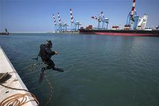 A scuba diver jumps in the water at the port of the northern city of Haifa April 23, 2013. REUTERS/Ronen Zvulun