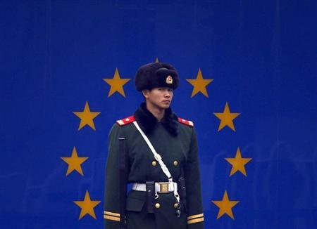 A paramilitary policeman stands guard at the entrance to the European Union embassy in central Beijing December 13, 2011. REUTERS/David Gray/Files