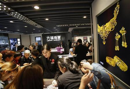 Attendants serve customers inside a jewellery store at Hong Kong's Mongkok district April 23, 2013. REUTERS/Bobby Yip/Files
