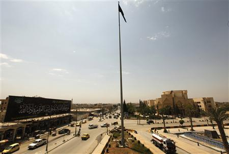 The flag of the Islamist Syrian rebel group Jabhat al-Nusra flies over the main square of the city of Raqqa, east Syria in this May 1, 2013 file photo. The most feared and effective rebel group battling Syrian President Bashar al-Assad, the Islamist Nusra Front, is being eclipsed by a yet more radical jihadi force. Al Qaeda's Iraq-based wing, which nurtured Nusra in the early stages of the rebellion against Assad, has moved in and sidelined the organisation, Nusra sources and other rebels say.REUTERS/Hamid Khatib/Files