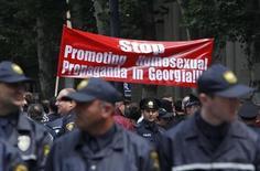 Полицейские охраняют акцию активистов в Тбилиси в Международный день борьбы с гомофобией 17 мая 2013 года. Консервативно настроенные граждане и политики в пятницу помешали защитникам прав сексуальных меньшинств провести в России и Грузии акции в поддержку международного Дня против гомофобии. REUTERS/David Mdzinarishvili