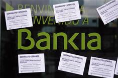 """A vandalized Bankia's bank office with papers stuck on it, is seen in Barcelona May 16, 2013. The papers read as """"Spanish 'corrallito' of LaCaixa and 52 other banks. More than a million people cheated, 8.25% of the Spanish population"""". REUTERS/Albert Gea"""