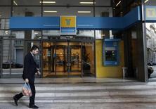 A man walks outside of the Hellenic Postbank's headquarters in Athens January 4, 2013. REUTERS/John Kolesidis