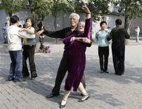 Elderly people dance during a morning exercise session at the Temple of Heaven park in Beijing in this October 10, 2009 file photograph. One of every four Chinese will be older than 60 by 2030, according to the Ministry of Civil Affairs. The costs of caring for China's rapidly expanding elderly population are likely to be too heavy a burden for the government, forcing Beijing to find cost-effective and creative ways to provide care in myriad localities. The self-help model being practiced among the 1,500 residents of Qiantun offers a cheaper and streamlined alternative to a state-run system. REUTERS/Grace Liang/Files