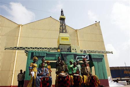 Traditional dancers perform in front of a model oil rig at a ceremony marking the start of new oil production at Takoradi, Ghana, December 15, 2010. REUTERS/Hereward Holland