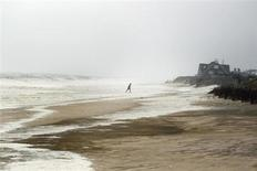 A man walks off the beach after photographing the stormy ocean in Sagaponack, New York August 28, 2011. REUTERS/Lucas Jackson