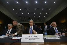 Apple CEO Tim Cook (C), CFO Peter Oppenheimer (L) and Apple Head of tax operations Philip Bullock appear before a Senate homeland security and governmental affairs investigations subcommittee hearing on offshore profit shifting and the U.S. tax code, on Capitol Hill in Washington, May 21, 2013. REUTERS/Jason Reed