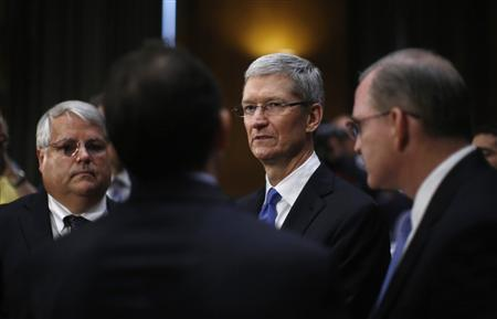 Apple CEO Tim Cook confers with staff during a break at a Senate homeland security and governmental affairs investigations subcommittee hearing on offshore profit shifting and the U.S. tax code, on Capitol Hill in Washington, May 21, 2013. REUTERS/Jason Reed