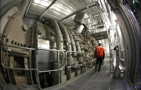 A man walks next to world's biggest gas turbine inside the gas-fired power plant of German utility giant E.ON in Irsching near the southern Bavarian town of Ingolstadt April 26, 2013. REUTERS/Michaela Rehle